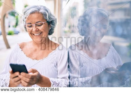 Middle age woman with grey hair smiling happy outdoors using smartphone