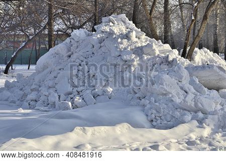 Snowdrift In The City Park. Municipal Communal Services Are Cleaning Snow On Roads And Alleys Of Cit