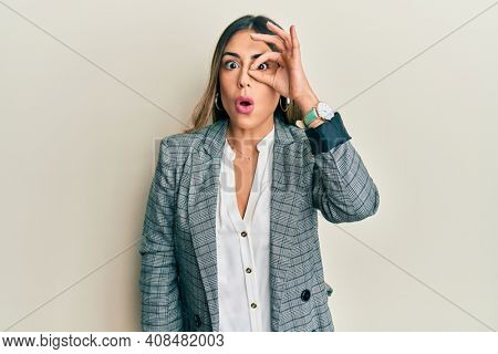 Young hispanic woman wearing business clothes doing ok gesture shocked with surprised face, eye looking through fingers. unbelieving expression.