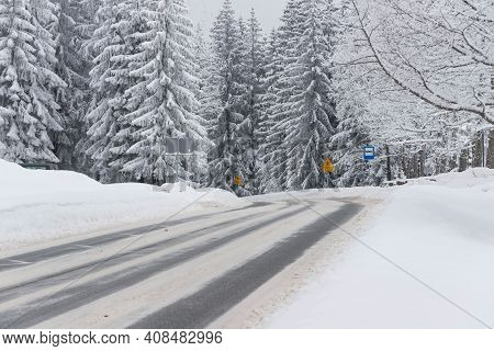 Jizera Mountains In Poland. Asphalt Road Covered With Broken Snow. Black Ruts. It Is The Provincial