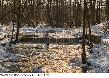 A Small River That Flows Through The Forest. Across The River, There Is A Dam That Creates A Waterfa