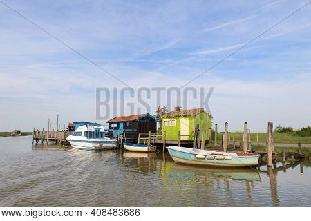 French wooden oyster huts at boat dock in landscape in the France Charente Maritime