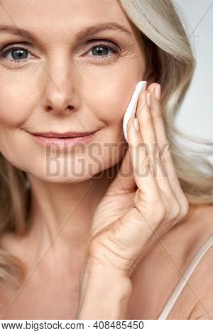 Pretty 50s Middle Aged Old Woman Holding Cotton Pad Sponge Cleansing Face Skin Purifying With Cleans