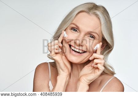 Happy 50s Mid Aged Mature Old Blonde Lady Applying Facial Cream On Face Skin Laughing Enjoying Anti