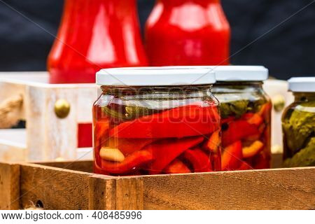 Wooden Crate With Glass Jars With Pickled Red Bell Peppers.preserved Food Concept, Canned Vegetables