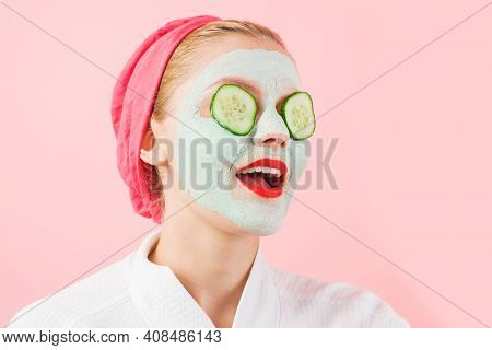 Woman With Cosmetic Mask On Face. Cucumber Slices On Eyes. Female With Facial Mask. Beauty Treatment
