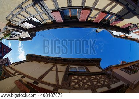 Fisheye View Of The Sky Above A Narrow Street In Riquewihr Town, Alsace, France