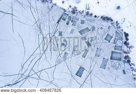 Aerial view to frozen lake with many playgrounds for ice hockey and skating rinks. Winter landscape.