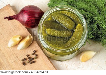 Delicious Pickled Cornichons In An Open Glass Jar, Dill, Onion, Garlic And Pepper On A Table. Whole