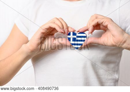 Love Greece. The Girl Holds A Heart In The Form Of The Flag Of Greece On Her Chest. Greek Patriotism