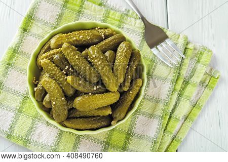 Close-up Of Pickled Cornichons In A Ceramic Bowl On A Green Checkered Napkin Over Table. Whole Gherk