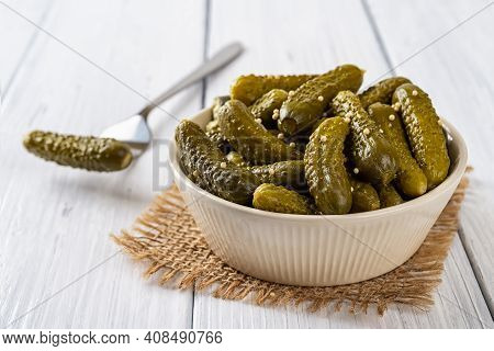 Crunchy Pickled Cornichons In A Beige Ceramic Bowl And One On A Fork On A White Wood Table. Whole Gr