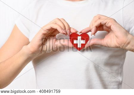 Love Switzerland. The Girl Holds A Heart In The Form Of The Flag Of Switzerland On Her Chest. Swiss