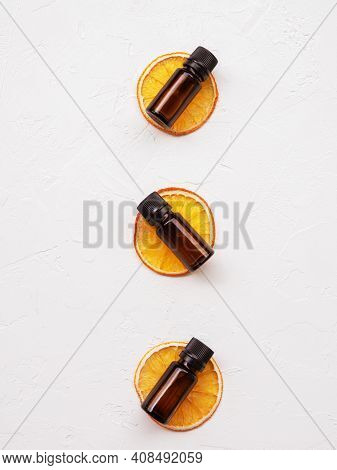 Beauty Natural Product. Bottles Of Citrus Essential Oil On Slices Of Dried Orange Composition On A W