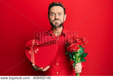 Middle age man holding anniversary present and bouquet of flowers puffing cheeks with funny face. mouth inflated with air, catching air.
