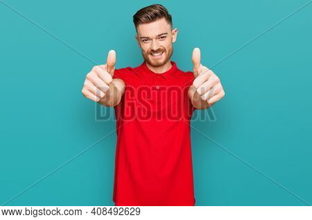 Young redhead man wearing casual clothes approving doing positive gesture with hand, thumbs up smiling and happy for success. winner gesture.