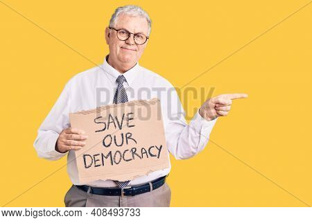 Senior grey-haired man wearing business clothes holding save our democracy protest banner smiling happy pointing with hand and finger to the side