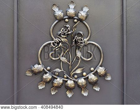 A Gilded Wrought Iron Pattern Of Roses, Leaves And Monograms On A Dark Iron Door. Closeup Photo
