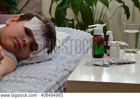 A Boy With A Cold Is At Home, Being Treated. There Are Medicines, Medicine, Throat And Nose Spray Ne