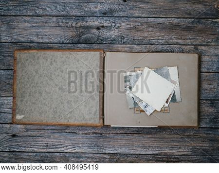 Vintage Home Photo Album Open On Dark Wooden Table. The Subject Of Family Values. The View From The