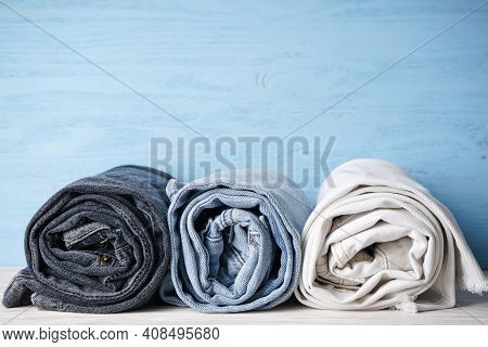 Jeans Are Stacked On A Blue Wooden Background, Space For Text. Stack Of Jeans Of Various Shades.