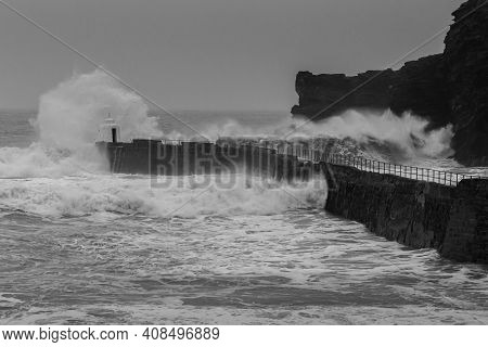 Big Wave Runs Into Harbour In Portreath Cornwall, Crashing Off Harbour Wall And Over The Monkey Hut.