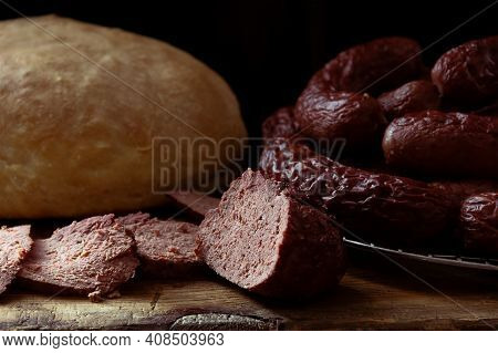 Homemade Venison Sausage On A Chopping Board And Bread In The Background
