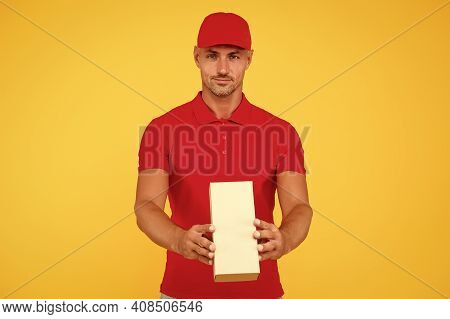 Service Plus Quality. Serious Guy Hold Parcel Yellow Background. Man Delivery Service. Express Couri