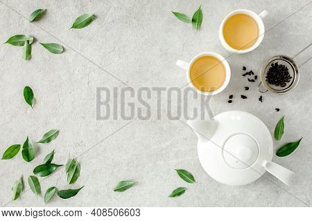 Herbal Tea With Two White Tea Cups And Teapot, With Green Tea Leaves. Flat Lay, Top View. Tea Concep