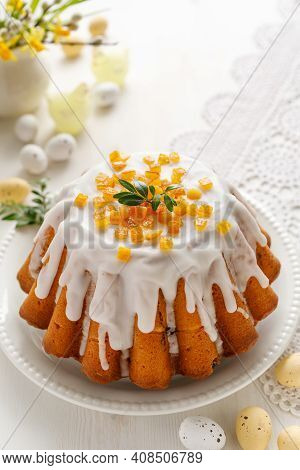 Easter Yeast Cake Covered With Icing With Candied Orange Peel On A White Plate Close Up View. A Trad