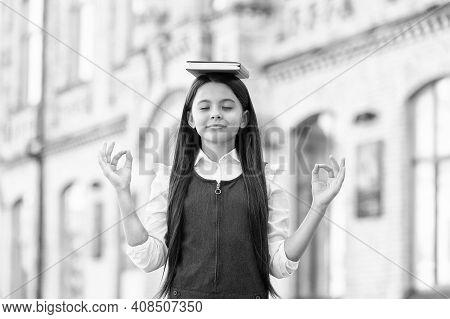 Calm The Mind. Little Child Do Meditation Outdoors. Small Girl Do Mudra Hands Holding Book On Head.