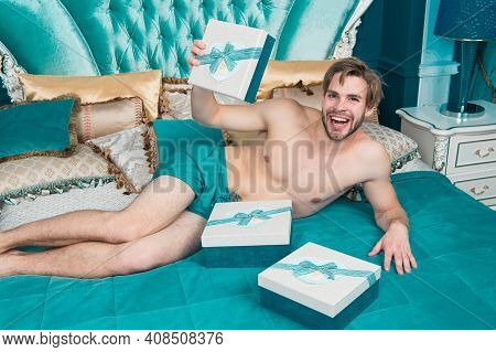 Receiving A Surprise Gift. Happy Man Got Birthday Surprise. Sexy Man Holding Gift Box In Bed. Happy