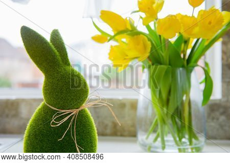 Cute Green Grass Bunny Rabbit And Bouquet Of Fresh Spring Yellow Tulips And Daffodils Flowers On The