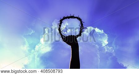 Hand Holding Crown Of Christ On Blue Sky With Clouds, Hand Of Christ, Christian Religion Concept