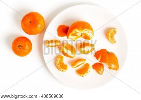 Peeling Tangerines Or Clementines In White Plate, Isolated On White Background