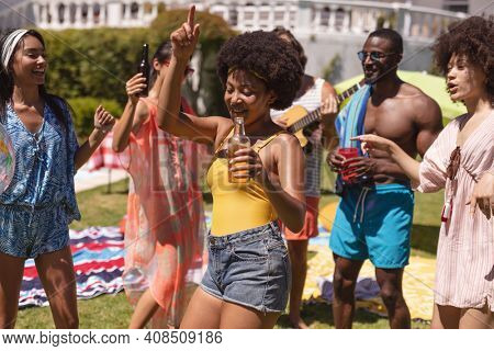 Diverse group of friends having fun and dancing at a pool party. Hanging out with drinks and dancing on the garden lawn in summer.
