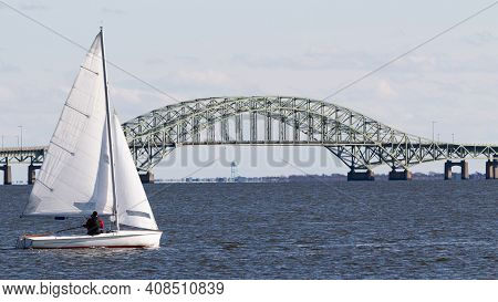 Sailboat Sailing With The Great South Bay Bridge In The Background And The Water Tower On Frie Islan