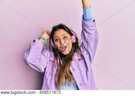 Young hispanic girl dancing and listening to music using headphones afraid and shocked with surprise and amazed expression, fear and excited face.