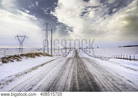A Rural Gravel Road Along Power Lines And Electrical Transmission Towers In Rocky View County Albert