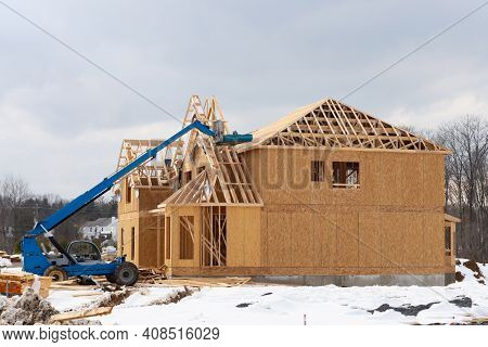 Forklift At A Construction Site Of A Plywood House Wood New