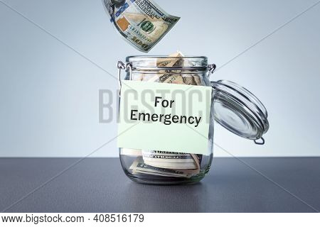 Crisis Fund.  For Emergency Written On A Jar With Dollars Banknotes Money.