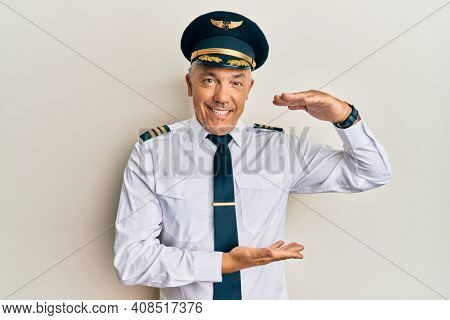 Handsome middle age mature man wearing airplane pilot uniform gesturing with hands showing big and large size sign, measure symbol. smiling looking at the camera. measuring concept.