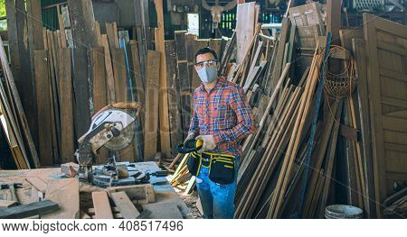 A Carpenter Is Working In A Woodworking Office.caucasion White Male Carpenter Using Electric Circula