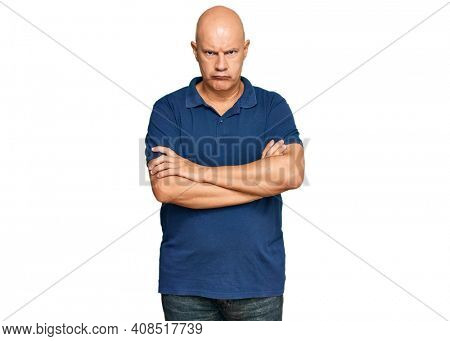 Middle age bald man wearing casual clothes skeptic and nervous, disapproving expression on face with crossed arms. negative person.