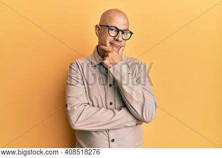 Middle age bald man wearing casual clothes and glasses with hand on chin thinking about question, pensive expression. smiling with thoughtful face. doubt concept.
