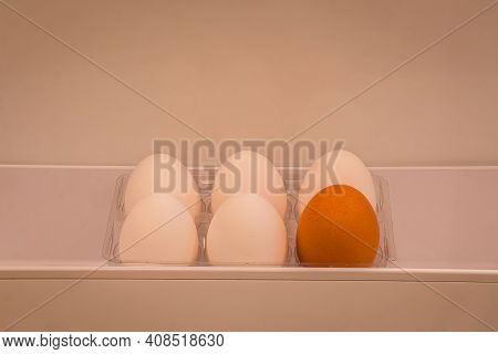 Half A Dozen Organic Eggs, 5 White And 1 Brown Kept In A Fridge Door