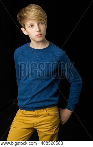 Handsome Blond Stylish Teenage Boy. Handsome Teenager Wearing Blue Pullover And Yellow Pants Posing