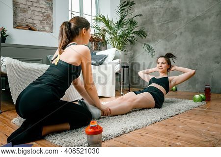Two Women Friends At Home Chatting, Smiling And Makes Sports. Cheerful Athletic Woman Presses, And T