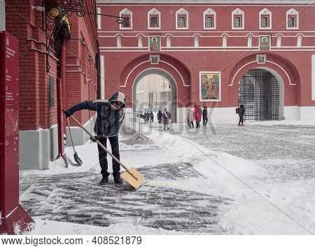 Moscow. Russia. February 12, 2021. A Man Removes Snow From The Sidewalk With A Wooden Shovel During