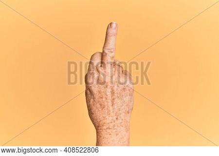 Senior caucasian hand over yellow isolated background showing provocative and rude gesture doing fuck you symbol with middle finger